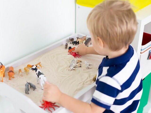 Мальчик играет с песком