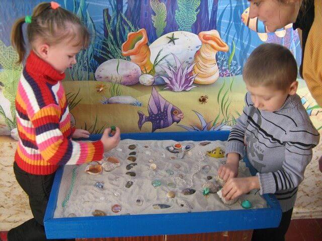 Мальчик с девочкой играют с песком