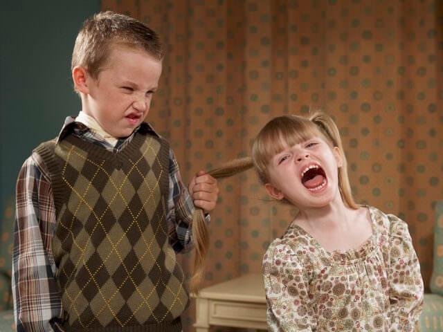 Мальчик дергает девочку за волосы