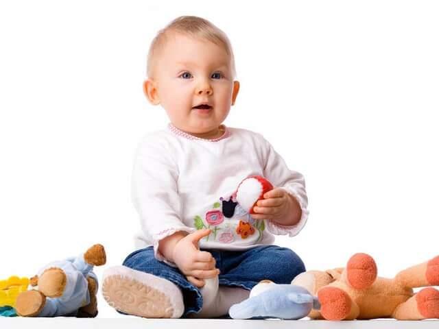 Ребенок сидит с игрушками