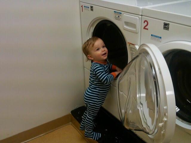 Малыш возле стиральной машины