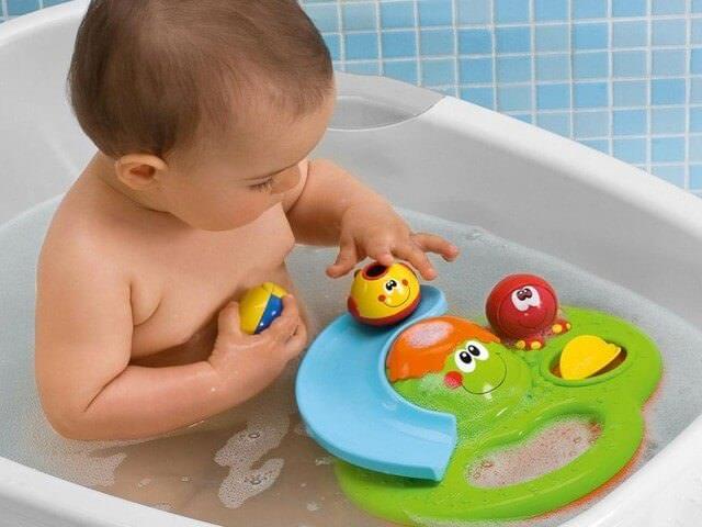 Малыш купается в ванночке