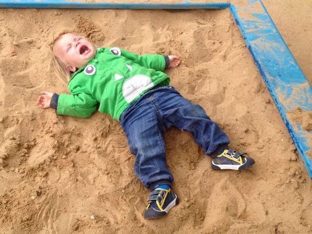 Мальчик лежит в песочнице