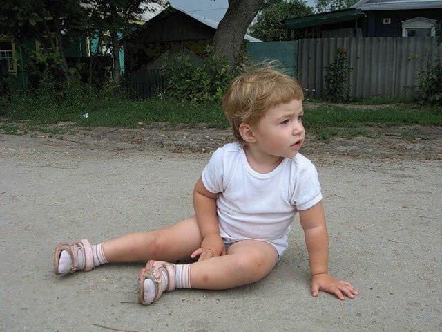 Ребенок сидит на дороге