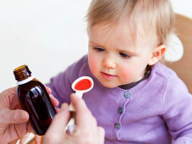 Ребенок пьет микстуру от кашля