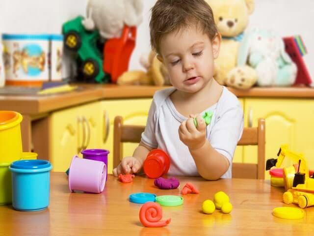 Малыш изучает пластилин