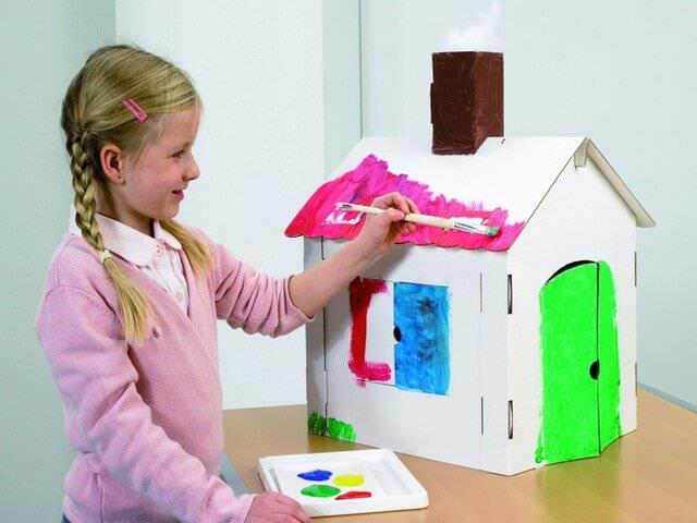 Девочка разукрашивает дом из картона