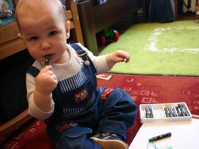 Мальчик рисует восковыми мелками