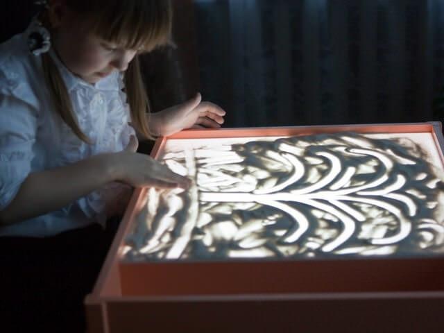 Девочка рисует дерево на песке