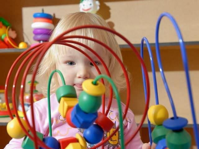 Девочка играет с игрушкой
