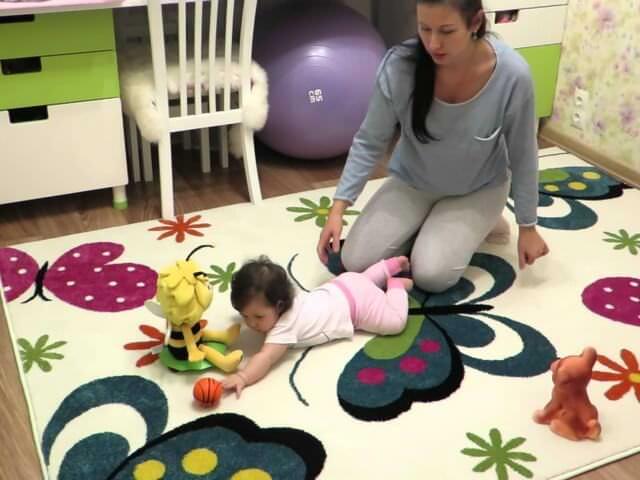 Девочка ползает на ярком ковре