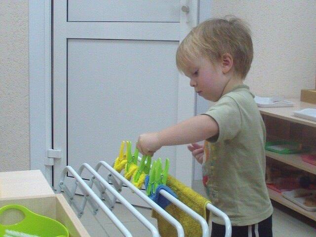 Малыш играет с прищепками