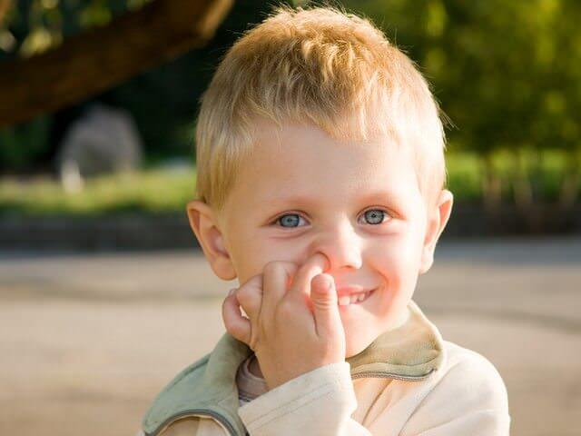 Ребенок на улице ковыряется в носу