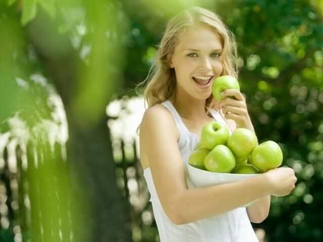 Женщина кушает яблоки