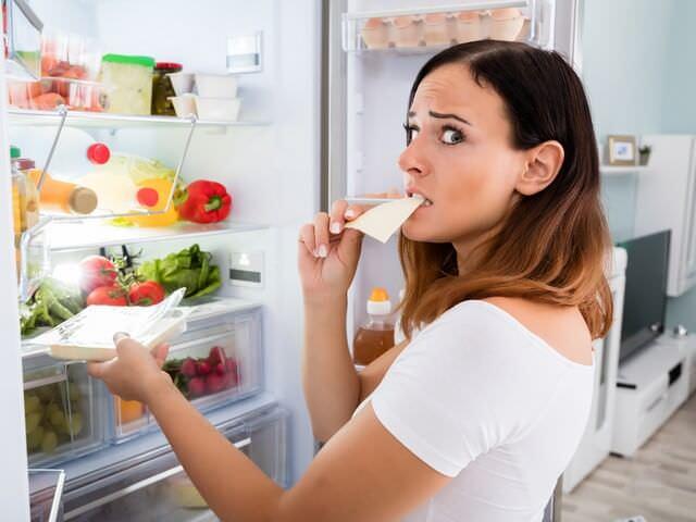 Женщина стоит возле открытого холодильника