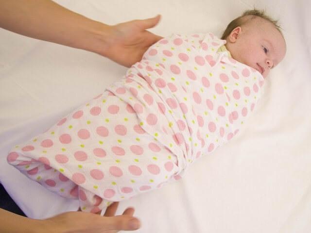 Младенец лежит на кровате