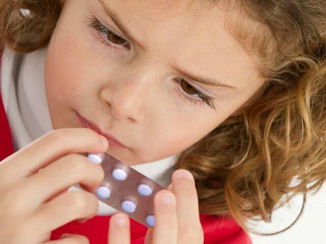Девочка рассматривает упаковку с лекарствами