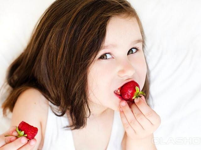 Ребенок кушает ягоды