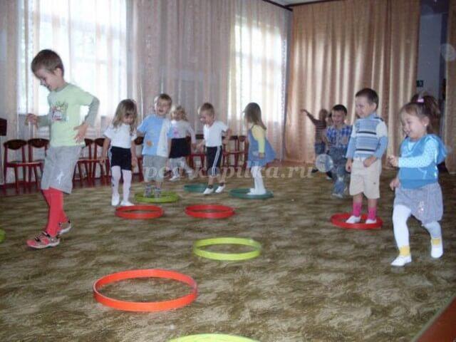 Дети играют с разноцветными обручами